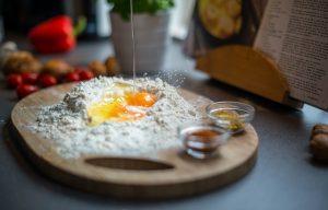 Brett mit Weissmehl, zwei Eiern in der Mitte und zwei kleinen Glasschälchen an der Seite mit Gewürzen