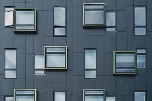 Fassade eines modernen Wohnblocks in grauen Platten mit rechteckigen und viereckigen Fenstern