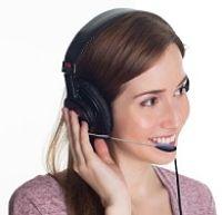 Junge Frau mit Headset die lächelt und mit ihrer linken Hand das Headset berührt