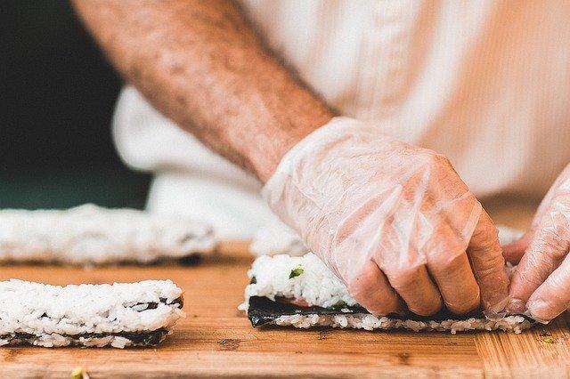 eine Person mit weißen Gummihandschuhen die gerade sushi Rollen macht