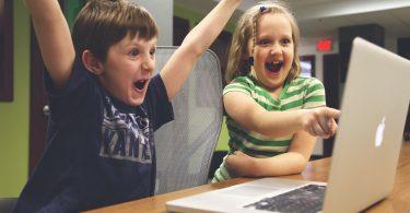 Ein Junge und ein Mädchen die vor Freude Jubeln und das Mädchen zeigt auf etwas auf dem Bildschirm eines grauen Apple Laptops
