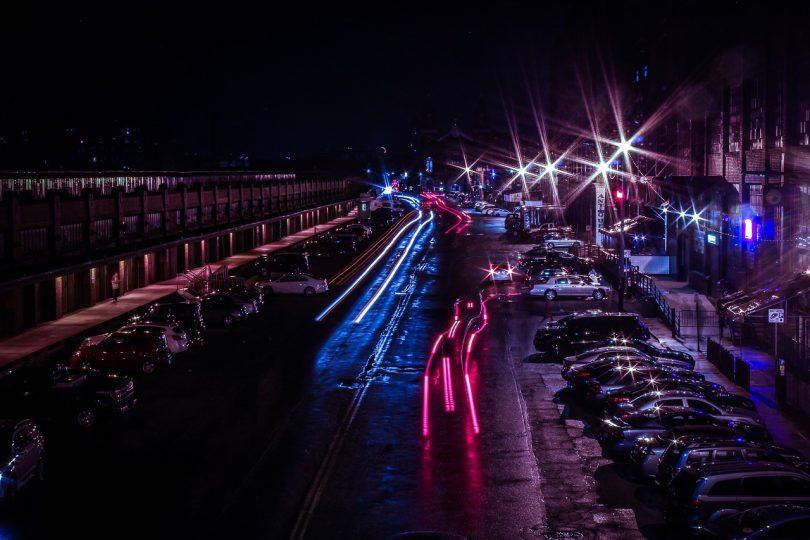 Strasse einer Großstadt bei Nacht mit roten blauen Lichtern der Autos und Parkplätze links und rechts