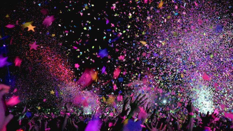 Konfetti in verschiedenen Farben und Sternformen das in einer Diskothek von der Decke fällt, die Menschenmenge hebt die Arme in die höhe
