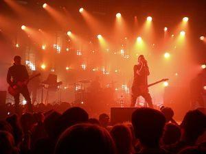 Rockkonzert: Disco voller Leute die auf den Sänger mit Gitarre under Gelb-orangen Lichtern steht