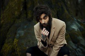 Mann mit langem dunklen Bart, mittellangen Harren und einem hellen Blazer für ein Foto posiert
