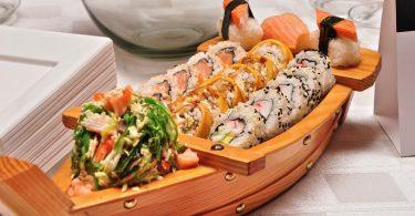 Kleines Holzschiff mit verschiedenen Sorten von Sushi darin