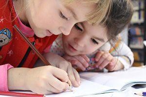 Zwei kleine Mädchen die über ein Heft gebeugt sind, eines malt etwas mit einem braunem Stift und die andere beobachtet sie fröhlich