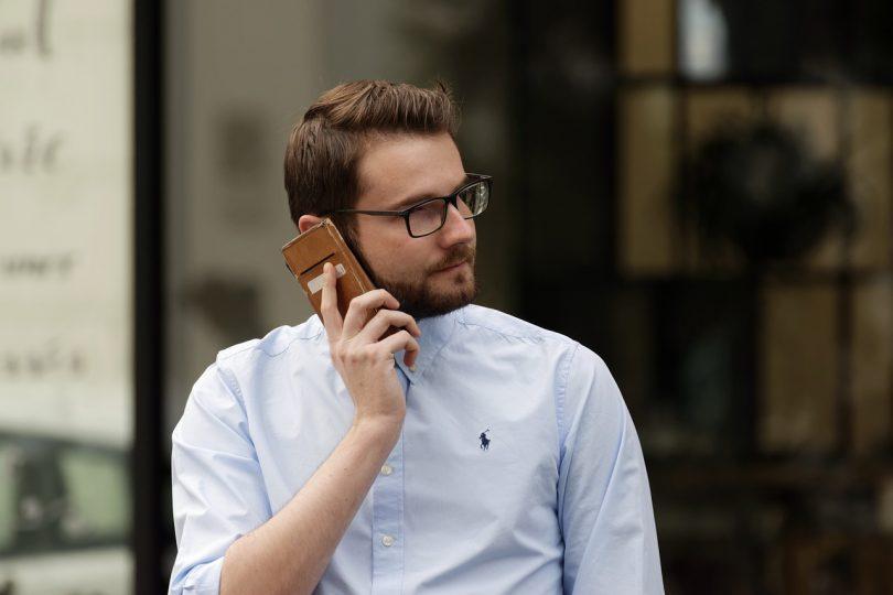 Man mit hellblauem Hemd und Brille der mit seinem Handy telefoniert