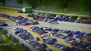 Grosse Parkplatzanlaga umgeben von Wiese und Bäumen mit geparkten Autos und LKWs