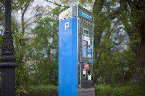Ein blauer Parkautomat neben einer Laterne und grüne Bäume im Hintergrund