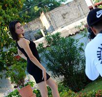 juge Frau mit schwarzem Minikleid die in einem Garten für einen Fotografen posiert