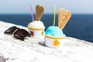 schwarze Sonnenbrille neben zwei Eisbechern, jeweils eine weisse Kugel und eine blaue Kugel mit einer herzförmigen Waffel und einem Smiley in der Mitte