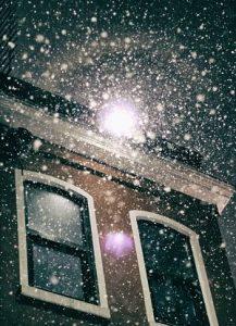 Foto nach oben auf den Schneefall beleuchtet von einer Laterne