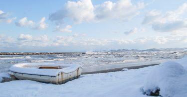 ein Fischerboot an einem beschneitem Strand
