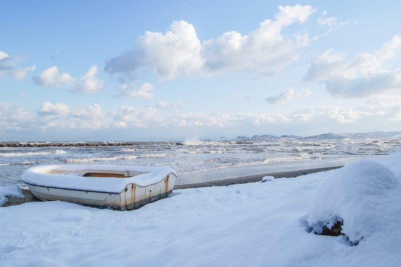 ein Fischerschiff an einem beschneitem Strand