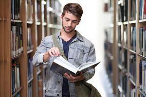 Ein junger Mann der gerade eine Seite eines grossen Buches umschlagen will während er durch eine Bibliothek läuft