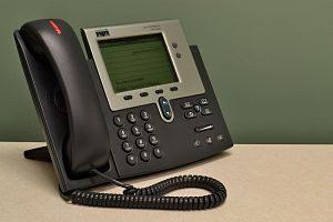 Normales Tastentelefon in schwarz und metallic auf einem hellem Tisch