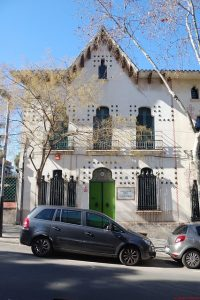 ein typisch ländliches Haus, weiss mit Verzierungen, grossen Fenstern mit grünen Fensterläden an einer Strasse in Horta