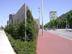 eine moderne bepflanzte Mauer die nach hinten immer breiter wird und rechts und links verlaufen große Alleen