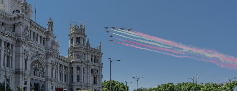 sieben Militärflugzeuge die in Dreiecks Formation die spanische Flagge mit Rauch über einem Rathaus überfliegen