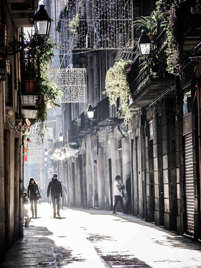 Fussgängerzone in Barcelona, ein Pärchen läuft unter der warmen Wintersonne die Gasse entlang, ein Teil der Weihnachtsbeleutung ist schon aufgehängt