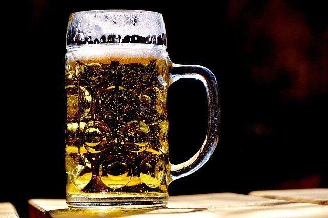 ein fast voller Bierkrug auf einem Holztisch