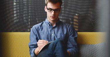 ein junger Mann mit schwarzer, eckiger Brille, Jeans und blauem Hemd sitzt auf einer gelben Bank und notiert etwas ein einem Heft