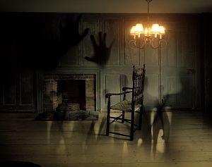 ein Zimmer mit einem Holzstuhl vor einem Kanin unter einer Lampe und die Schatten mehrere Geister und zwei grosse Schattenhände an der Wand