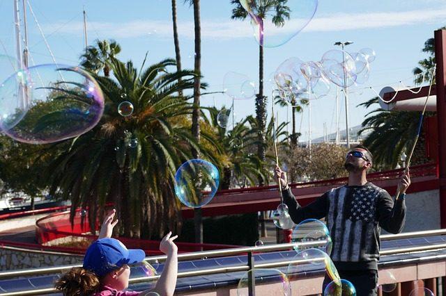 ein Mann der an der Promenade mit Hilfe von zwei Stöcken und einem Seil riesige Seifenblasen macht
