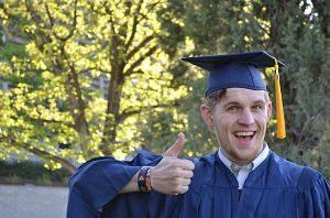 ein junger Mann der den Daumen nach oben zeigt und lächelt weil der seinen Bachelor bestanden hat, ausserdem trägt er die traditionelle Toga und Hut in blau