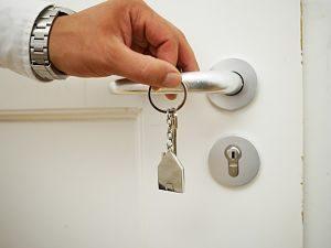 eine Hand mit silberner Uhr und weissem Ärmel die einen Schlüssel mit einem kleinem Hausschlüsselanhänger vor einer Türklinke hält