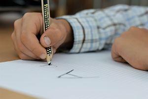 der arm eines Jungen mit einem blau-grau kariertem Hemd, er hält einen schwarzen Stift in der Hand und hat auf ein kariertes Blatt ein grosses und ein kleines a geschrieben