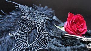 Eine gewebte Maske, Handschellen und eine rote Rose auf einer grauen Decke