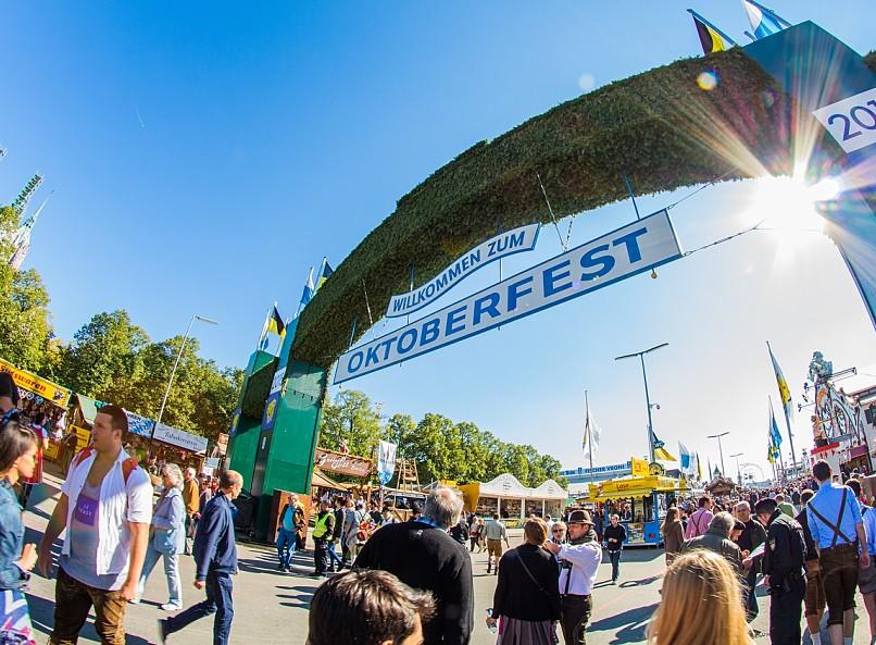 Eintritt ins Gelände des Oktoberfestes: ein grosser Heckenbogen und darunter steht auf zwei verschiedenen Schildern Herzlich willkommen zum Oktoberfest