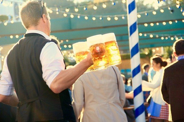ein Kellner in weißem Hemd und schwarzer Weste der vier Bierkrüge in der Halt hält und durch die Menschenmengen läuft