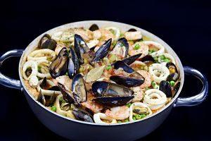 """blauer Topf mit typisch peruanischer """"Paella"""", mit Tinoenfischringen, Garnelen, Miesmuscheln, Reis, etc"""