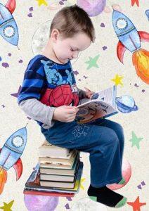 ein Junge mit einem Spiderman-T-Shirt der auf einem Turm von Büchern sitzt und ein Buch ansieht