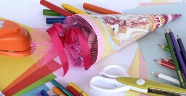 Eine kleine, rosten Schultüte auf einem weissen Tisch , drum herum liegen Scheren, Buntstifte, bunte Kartons etc