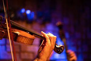man sieht unter blauen Beleuchtung eine Hand die eine Geige hält
