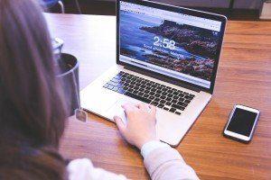 Frau die an einem Holztisch sitzt eine Tasse Tee in der linken Hand hält und mit der rechten Hand an einem Laptop arbeitet