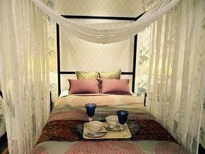Himmelbett mit zwei roten und zwei grünen Kissen und am unteren ende des Bettes ein rechteckiges Tablett mit zwei blauen Weingläsern und zwei Schüsseln mit Unterteller und Löffel