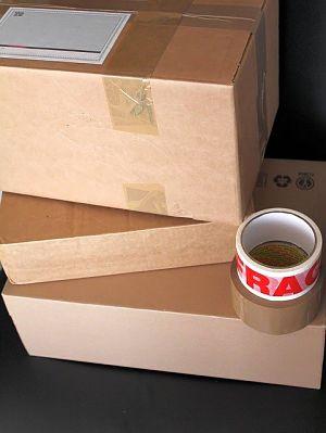 drei aufeinander gestapelte Umzugskartons und auf der Ecke der untersten Schachtel lieben sei rollen Klebefilm ein braunes und eins mit roter Schrift zerbrechlich