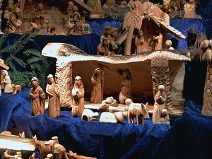 ein Verkaufsstand auf einem Weihnachtsmarkt mit Krippen aus holz auf einem blauem Tuch, im Vordergrund eine komplette Krippe mit Maria, Josef, Jesus, die Hirten, ein Esel usw