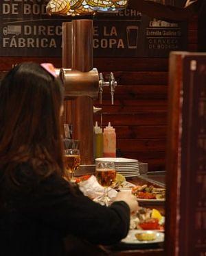 Frau mit schwarzem Pullover und langen braunen Haaren die an einer Bar Tapas isst und Wein trinkt
