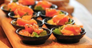 ein rechteckiges Holzbrett mit mehreren kleinen schwarzen porzelanschüsseln gefüllt mit Sushi