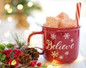 eine rote Tasse auf der in weiss believe steht mit mehreren Schneeflocken drumherum, ein weiss-rotes Röhrchen und weihnachtliche Dekoration neben der Tasse wie ein kleiner Tannenzweig, Misteln, Tannenzapfen und Lichter