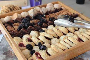 ein Holztablett mit verschiedenen Keksen, Brown und frischen Rombeeren und auf jeder Seite eine Brotzange aus metal