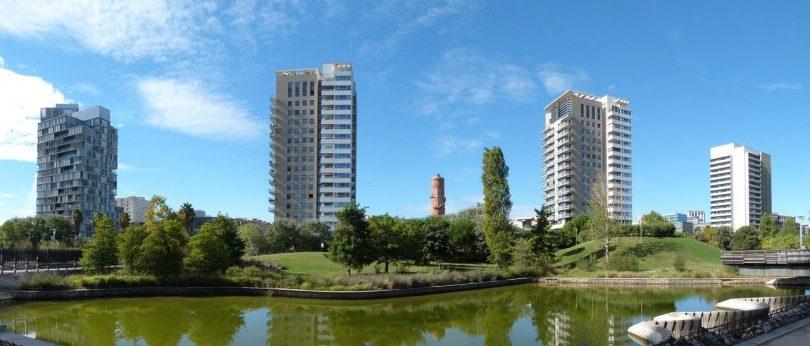 drei Hochhäuser mit Wohnungen an der diagonal de mar mit einem Teich davor und von bäumen umgeben