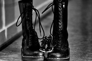 Erwachsenen dr Martens Stiefel in schwarz und darauf ein paar der kleinsten Grösse der selben Stiefel