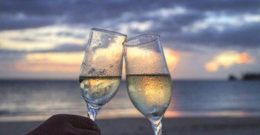 zwei Sektgläser die miteinander anstossen im Hintergrund das Meer , Wolken und ein Sonnenuntergang